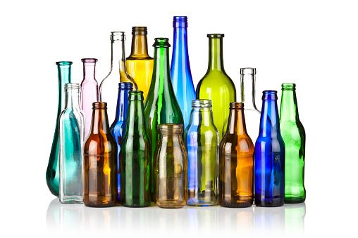 multi colored glass bottles standing together with a white background
